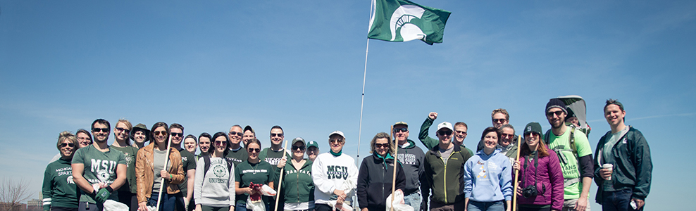 Spartan volunteers stand around flag -